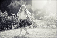 Cute little girl with skirt, dancing and swirling around, summer Royalty Free Stock Images