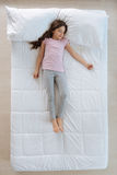 Cute little girl sleeping on the bed Stock Photos