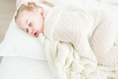 Cute little girl sleeping covered in white blanket. royalty free stock image