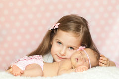 Cute little girl with a sleeping newborn sister Stock Images