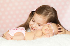 Cute little girl with a sleeping newborn sister Royalty Free Stock Photos