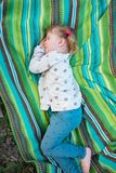 Cute little girl is sleeping sweetly on a coverlet. In a park. Happy childhood in nature Royalty Free Stock Photography