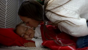 Cute little girl sleeping under Christmas tree at morning stock footage