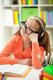 Cute little girl is sleeping while wearing glasses. A little  red-haired girl bored with her homework Royalty Free Stock Images