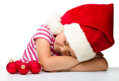 Cute little girl is sleeping wearing santa hat Stock Image