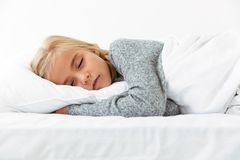 Cute little girl sleeping on white pillow in gray pajamas havin. G pleasant dreams Stock Photo