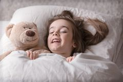 Little cute girl in bed with toy royalty free stock image