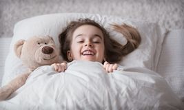 Little cute girl in bed with toy stock photos