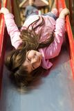 Cute Little Girl on Slide. Cute little girl smiles as she hangs head first on slide in playground.  Another child is visible in blurred background Royalty Free Stock Photography