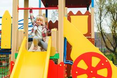 Cute little girl on a slide, outdoors. Adorable funny girl at modern colorful playground. Happy and healthy childhood. Active royalty free stock photo