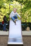 Cute little girl sliding at playground Royalty Free Stock Photos