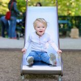 Cute little girl sliding at playground Stock Images
