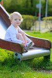Cute little girl sliding at playground Royalty Free Stock Images