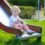 Cute little girl sliding at playground Stock Photo