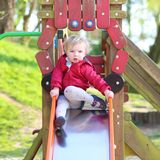 Cute little girl sliding at playground Royalty Free Stock Image