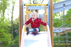 Cute little girl sliding at playground Royalty Free Stock Photography