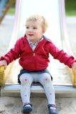 Cute little girl sliding at playground Stock Photos