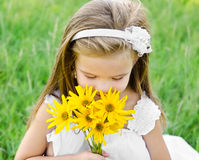 Cute little girl smelling flowers on the meadow Royalty Free Stock Images