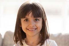 Cute little girl smiling looking at camera indoors, headshot portrait. Cute little girl smiling looking at camera indoors, playful preschool lovely beautiful royalty free stock image