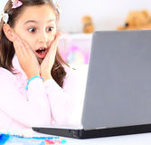 Cute little girl smiling and looking at laptop Stock Photo