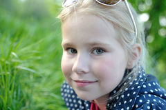 Cute little girl smiling in a park close-up. Blonde cute little girl smiling in a park close-up Royalty Free Stock Image