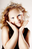 Cute little girl. Cute little smiling girl posing in crown, looking at camera Stock Images
