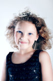 Cute little girl. Cute little smiling girl posing in crown, looking at camera Stock Photos
