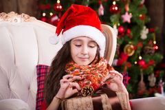Cute little girl smiling with present near the Stock Photos