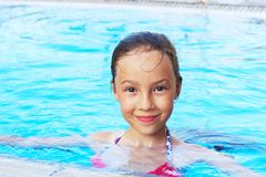 Cute little girl is smiling in swimming pool. Summer, vacation, Stock Photography