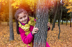Cute little girl smiling by the tree Stock Photos