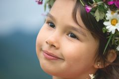 Cute little girl smilling while looking aside. With flowers over head royalty free stock image
