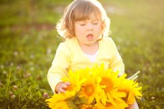 Happy child with bouquet of beautiful sunflowers. Cute little girl sneeze holding yellow sunflowers, outdoor portrait, allergy concept Stock Photography