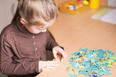 Cute little girl solving puzzles Royalty Free Stock Image
