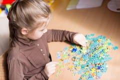 Cute little girl solving puzzles Stock Photos