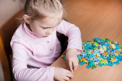 Cute little girl solving puzzles Stock Photography