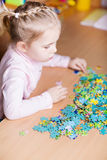 Cute little girl solving puzzles Royalty Free Stock Images