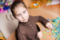 Cute little girl solving puzzles Royalty Free Stock Photo