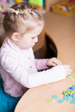 Cute little girl solving puzzles Stock Photos