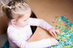 Cute little girl solving puzzles Stock Images