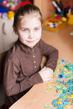 Cute little girl solving puzzles Royalty Free Stock Photos