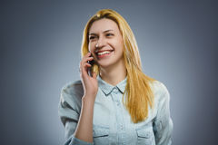 Cute little girl speaking on the cell phone. isolated on gray Stock Photography