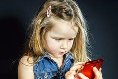 Cute little girl speaks using new cell phone. Stock Photo