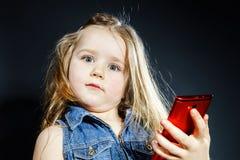 Cute little girl speaks using new cell phone. Stock Photos