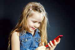 Cute little girl speaks using new cell phone. Royalty Free Stock Photography