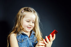 Cute little girl speaks using new cell phone. Stock Image