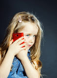 Cute little girl speaks using new cell phone. Royalty Free Stock Images