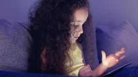 Cute Little Girl Spending Leisure Time Playing Mobile Game in the and Crushes the Bright Screen With Her Hand. Concept. Cute Child Entertaining With Tablet stock video