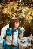 Cute little girl in a spring garden drinking tea Stock Photos