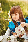 Cute little girl in a spring garden drinking tea Stock Images