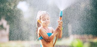 Cute little girl sprinkls a water for herself from the hose, makes a rain. pleasure for hot summer days stock photo